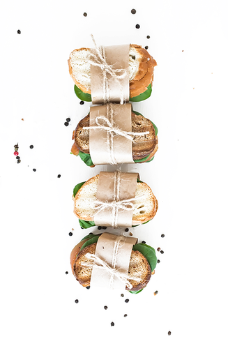 Decorative gourmet sandwiches wrapped in paper with twine